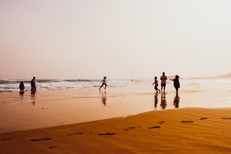 Silhouettes des personnes jouant en plage d'or ar?nac?e, Karpasia, Chypre photographie stock libre de droits