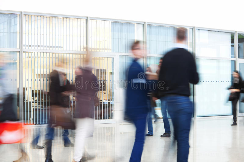 Silhouettes des personnes marchant dans l'immeuble de bureaux photo stock