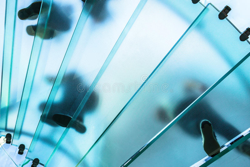 Silhouettes des personnes marchant sur un escalier en spirale en verre photos libres de droits