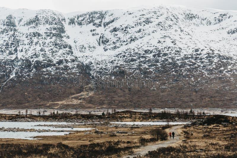 Silhouettes des personnes non identifiées marchant par les montagnes couronnées de neige et le loch en montagnes écossaises, Ecos image libre de droits