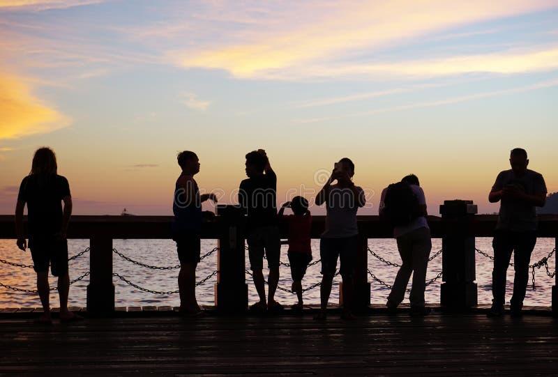 Silhouettes des personnes pendant le coucher du soleil photo stock