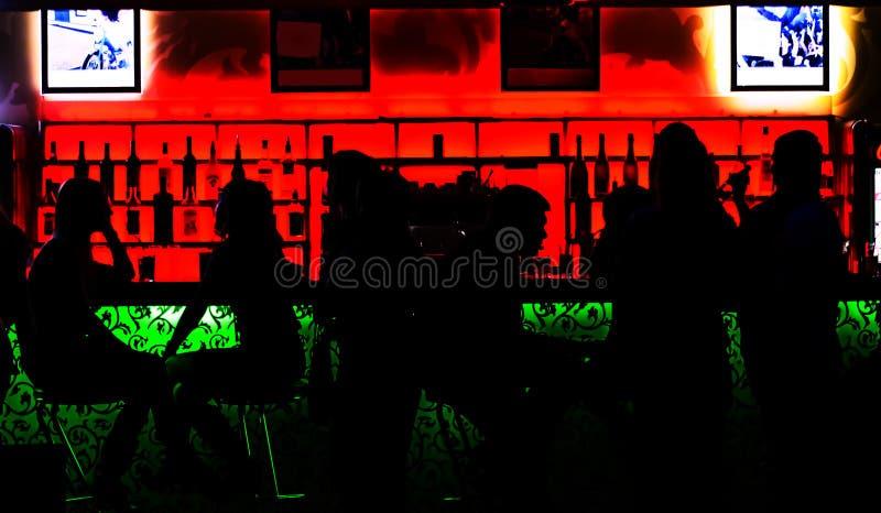Silhouettes des personnes s'asseyant à la barre image libre de droits