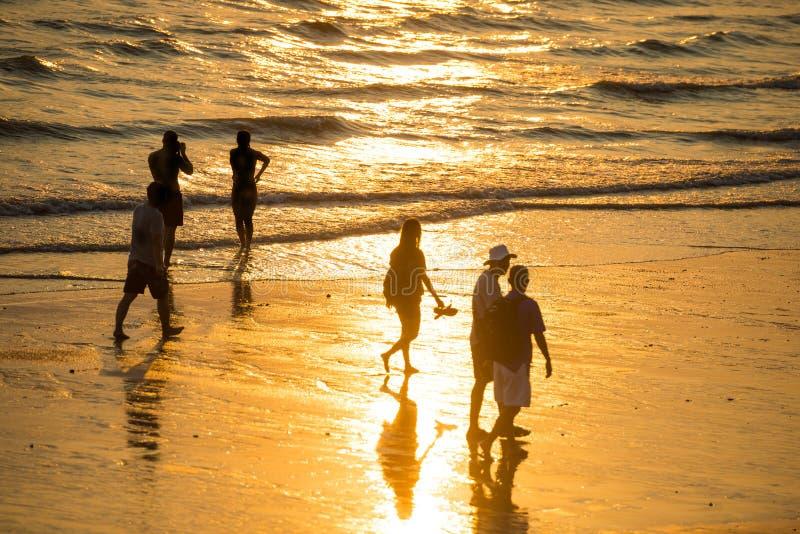 Silhouettes des personnes sur la plage au coucher du soleil image stock