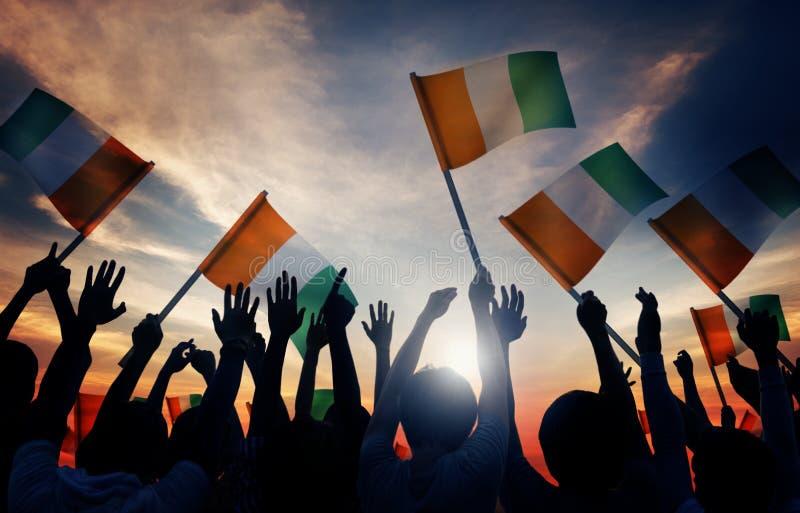 Silhouettes des personnes tenant le drapeau de l'Irlande photographie stock