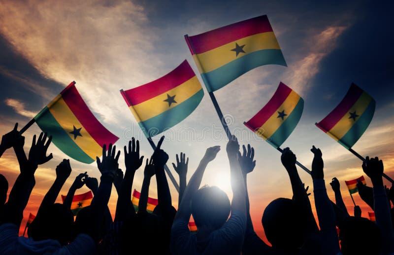 Silhouettes des personnes tenant le drapeau du Ghana photo stock