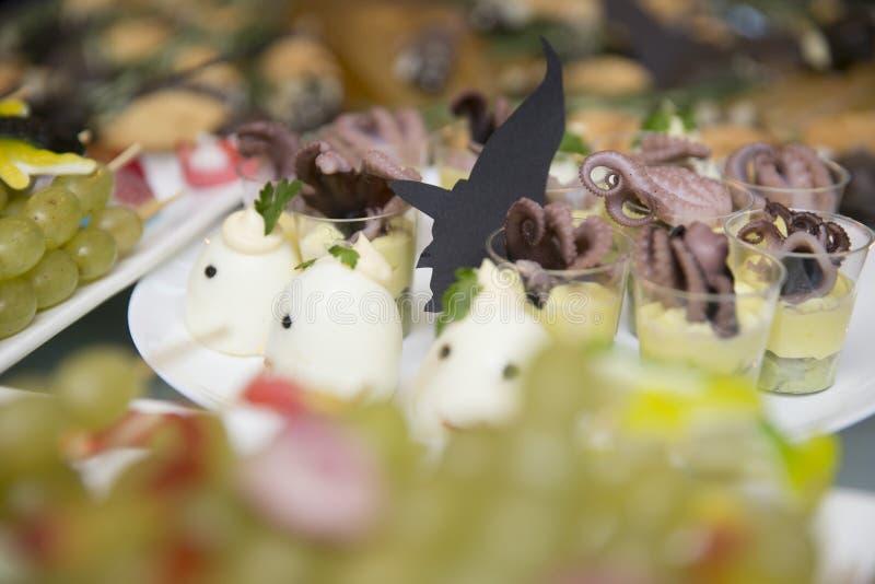 Silhouettes des sorcières parmi les oeufs à la coque et les casse-croûte bourrés de poulpe en verres photo libre de droits