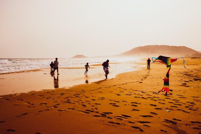 Silhouettes du jeu et du vol de personnes un cerf-volant en plage d'or ar?nac?e, Karpasia, Chypre photos stock