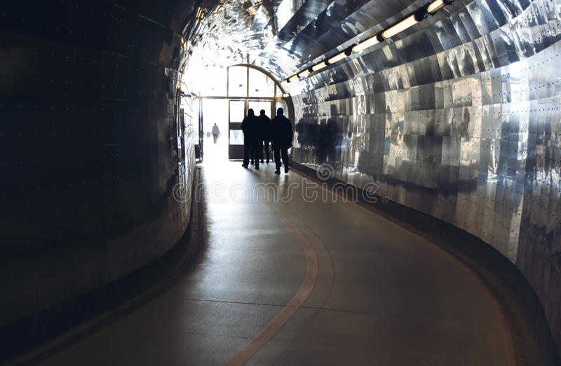 Silhouettes at the end of a tunnel for pedestrians and cyclists. In Stockholm, Sweden stock photo