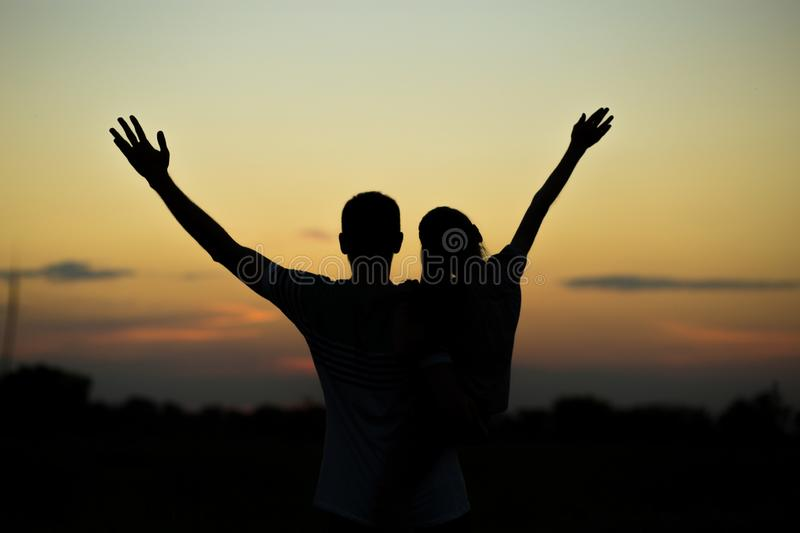 Silhouettes of father and daughter on his shoulders with hands up having fun, against sunset sky. royalty free stock image