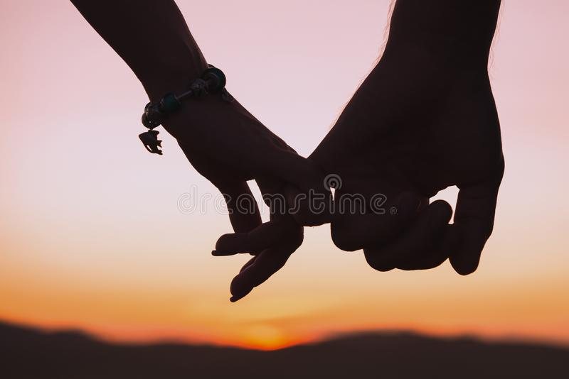 Silhouettes of female and male hands holding hands against background of setting sun. Relationships, love, date theme. Toned stock image
