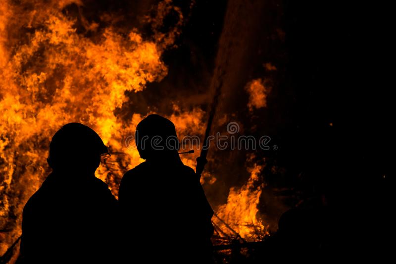 Silhouettes of fire fighters fighting a fire stock image