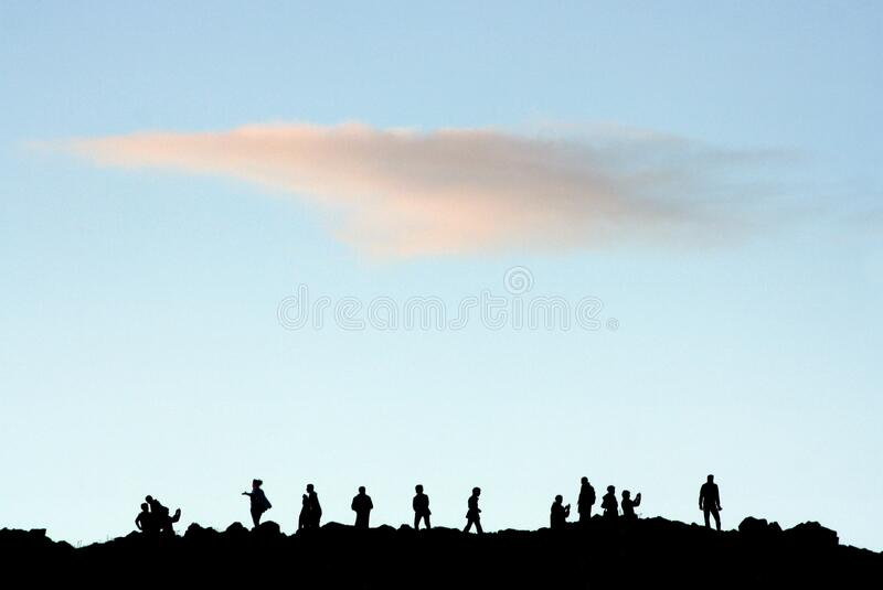 Silhouettes of folk at hill top gathering stock photo