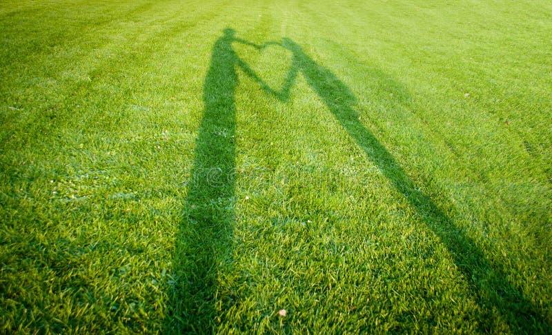 Silhouettes formant un coeur au-dessus d'herbe image stock