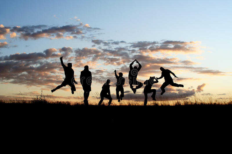 Silhouettes of friends jumping 2 stock images