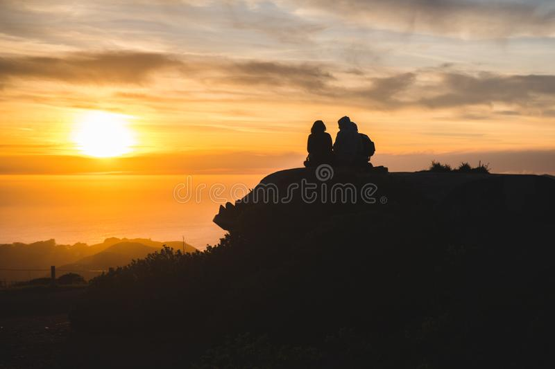 Silhouettes of friends travelers on top of a hill watching a beautiful sunset and talking, California royalty free stock photos