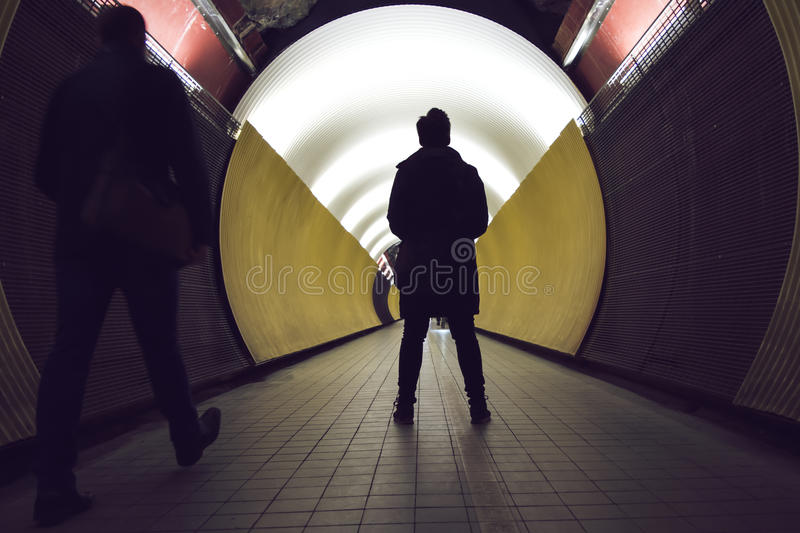 Silhouettes in front of a circular tunnel for pedestrians and cyclists royalty free stock photography