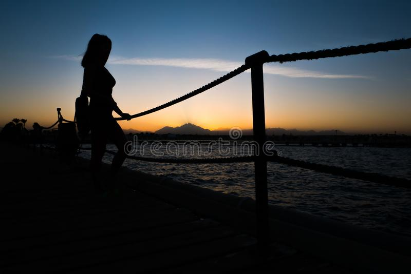 Silhouettes of a girl standing on a pier near the sea against the background of a sunset in the mountains. stock photos