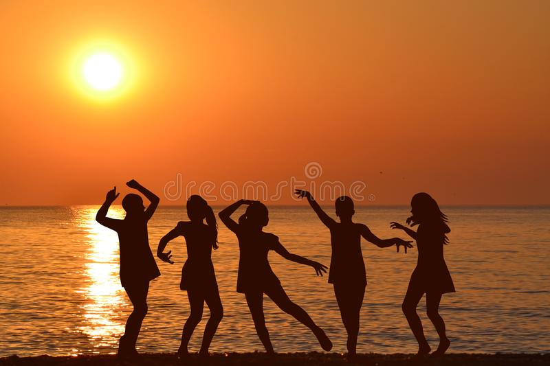 Silhouettes of girls dancing at the sunrise stock photography