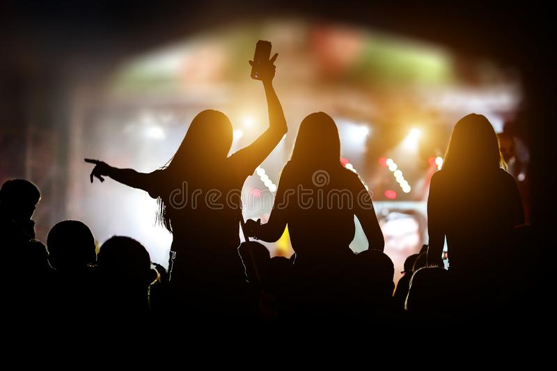 Silhouettes of girls at outdoor music show royalty free stock photo