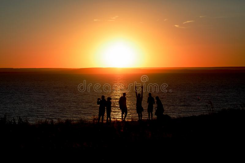 Silhouettes of a group of people watching the sunset over the river stock images