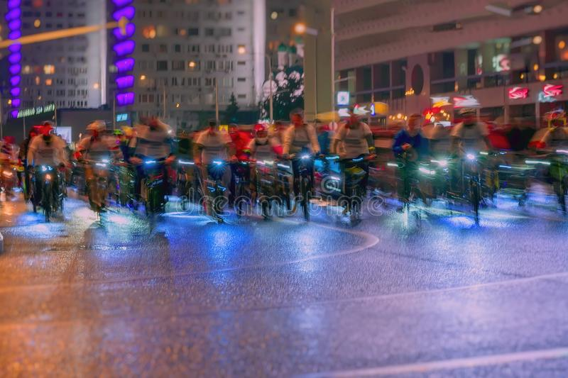 Silhouettes of group riding cyclists. Parade of bicyclists in city, night, abstract. Sport, fitness and healthy stock photography