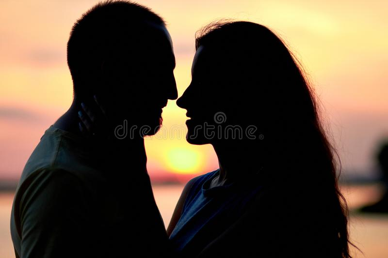 Silhouettes of a guy and a girl on a sunset background. Hugs of a couple in love. Lovers man and woman in each other`s arms. Coupl royalty free stock photo