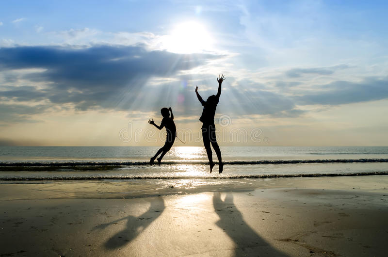 Silhouettes of happy brothers jumping with raised arms. Near beach at sunrise royalty free stock images