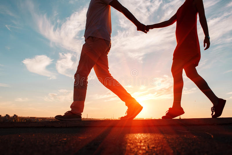 Silhouettes of happy couple running down at sunset, perfect love background. royalty free stock photo