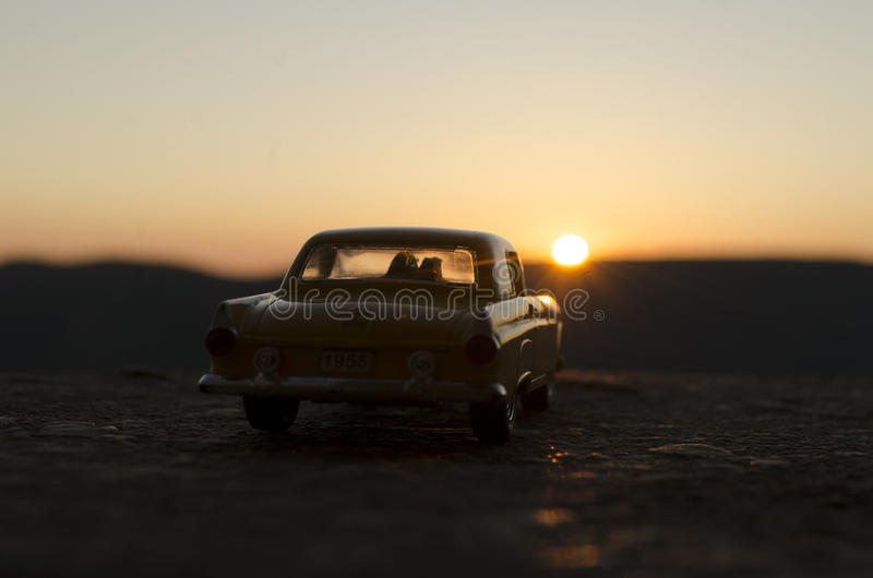 silhouettes of Happy Couple sitting in old vintage car at sunset time. Toy installation effect like reality. Selective focus royalty free stock photos