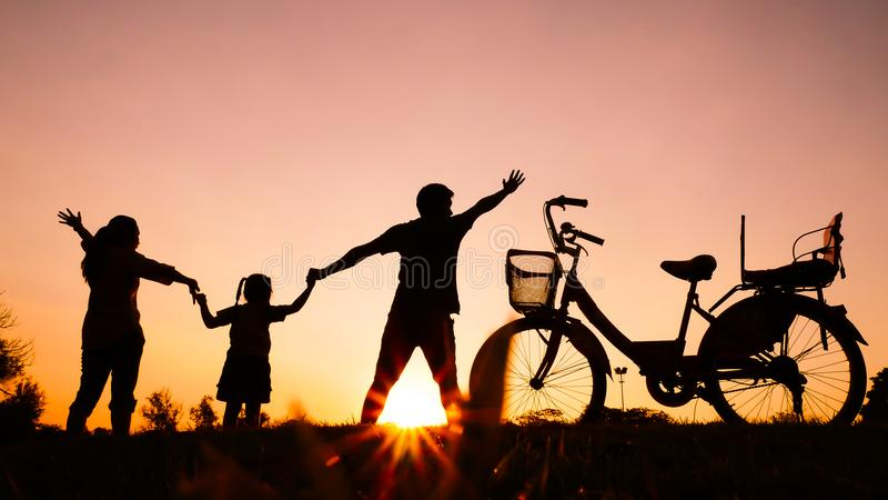 Silhouettes of happy families play together at the park in the e. Vening. with sun flare. Concept of friendly family stock photography