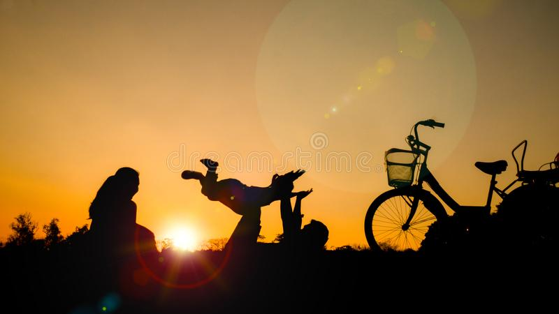 Silhouettes of happy families play together at the park in the e. Vening. with sun flare. Concept of friendly family stock images