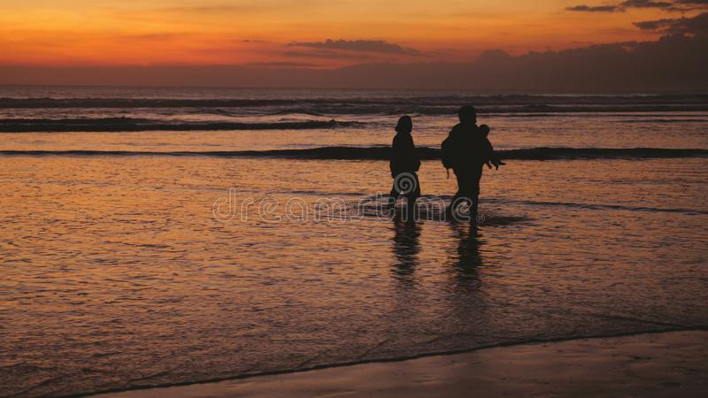 Silhouettes of happy family walking on sea coast during beautiful sunset. Silhouettes of happy family walking on sea coast during sunset royalty free stock images