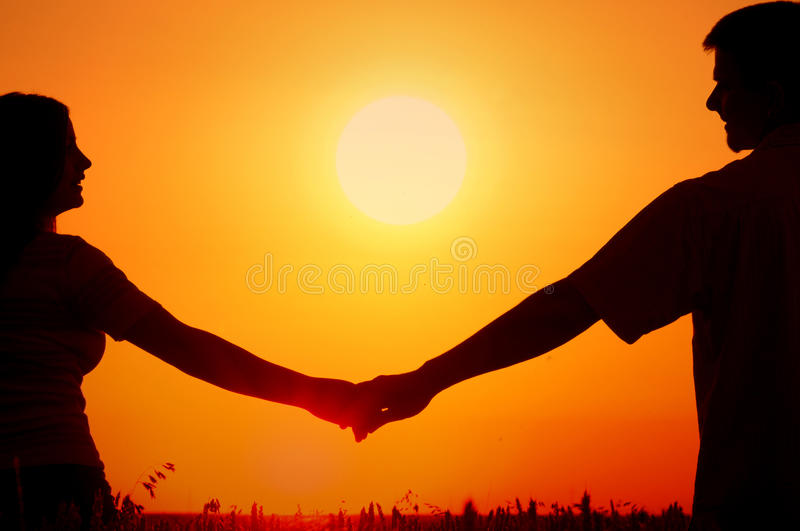 Silhouettes of happy smiling young couple in summer wheat field stock photo