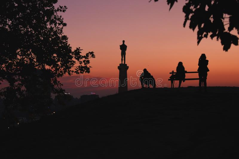 Silhouettes on the hill. Night shoot of silhouettes on famous hill of thinking in Kalemegdan old city of Belgrade people looking in statue Pobednik The Winner royalty free stock photos
