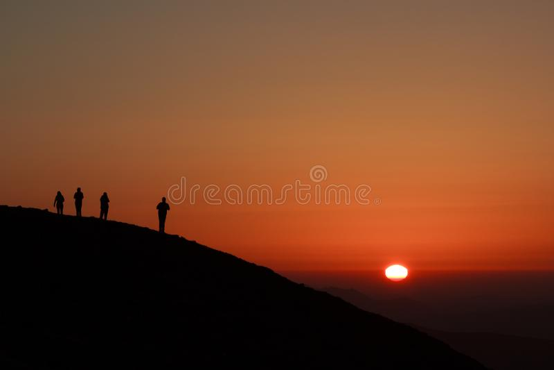 Silhouettes le long de la crête de montagne photo stock