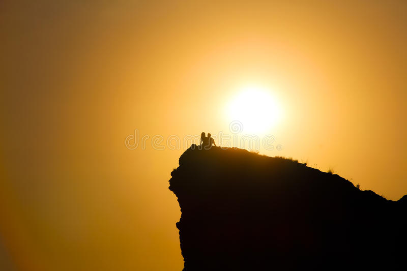 Silhouettes of lovers on sunset stock images