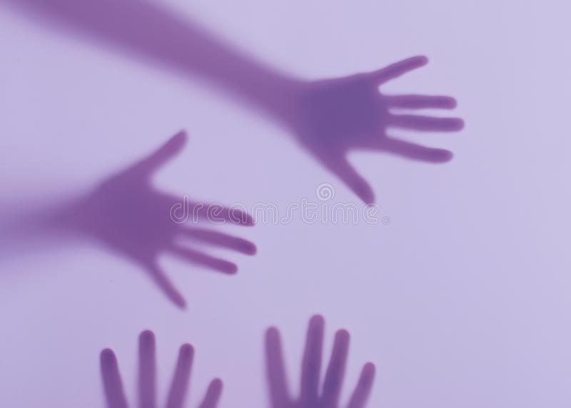 Male and female hands behind a frosted glass. Silhouettes of male and female hands. Conceptual scene stock images