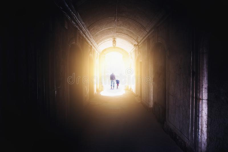 Silhouettes of man and child, father and daughter, walking into light from dark tunnel. Toned royalty free stock photos