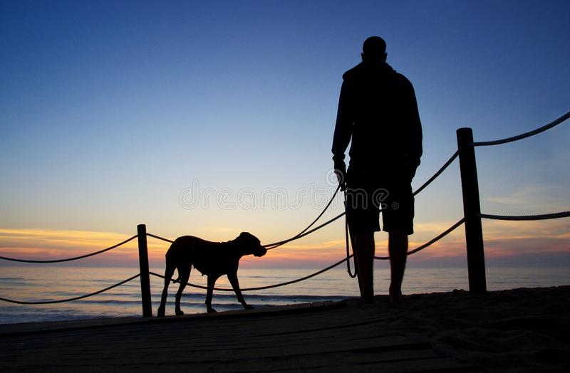 Silhouettes of a man and a dog. royalty free stock image