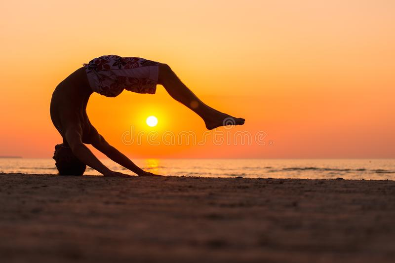 Silhouettes of a man jumping on a beach royalty free stock photos