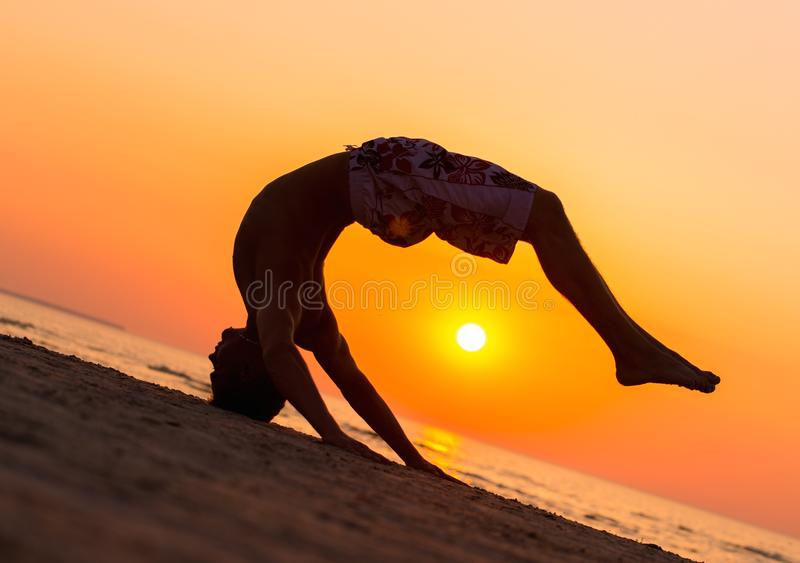 Silhouettes of a man jumping on a beach royalty free stock image