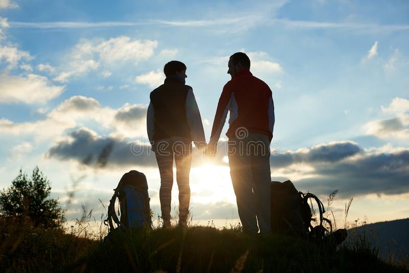 Silhouettes of man and woman looking at each other, holding hands against sunset in mountains royalty free stock photography