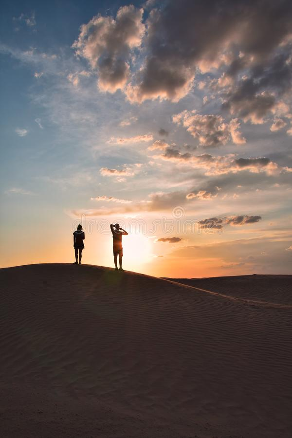 Silhouettes of man and woman on top of a sand dune in the Sahara desert. Enjoying the sunset royalty free stock image