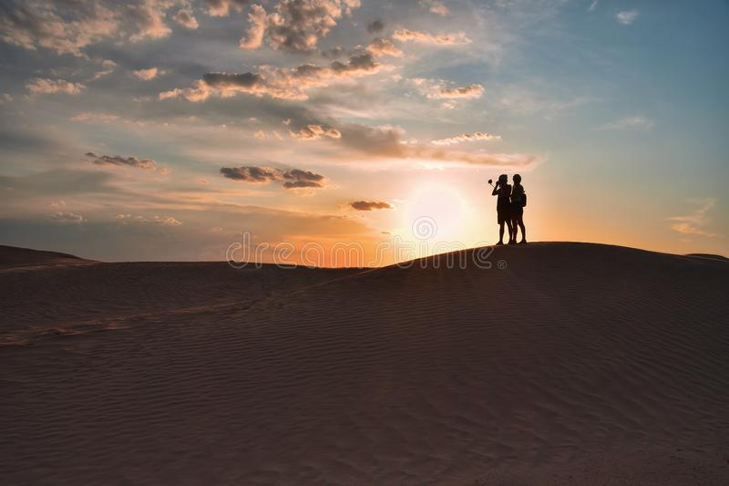 Silhouettes of a man and a woman on top of a sand dune in the Sahara desert. Take a selfie on a smartphone and enjoy the sunset stock photo