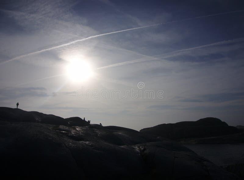 Silhouettes marchant devant le soleil images libres de droits