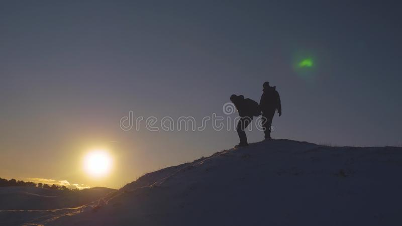 Silhouettes of men descending from high snowy mountain seeking adventure in glare of setting sun in winter. Concept of stock photos