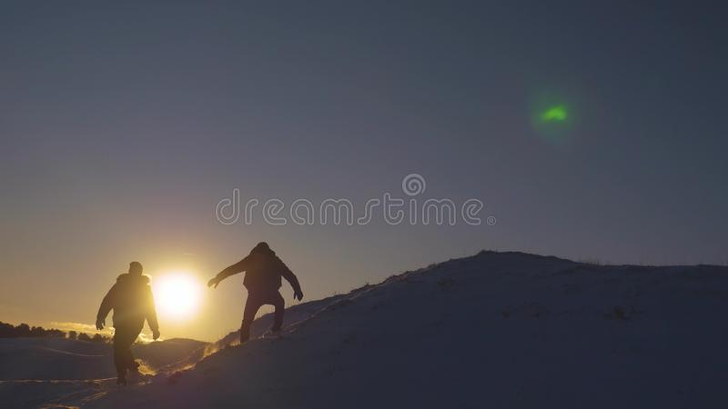 Silhouettes of men descending from high snowy mountain seeking adventure in glare of setting sun in winter. Concept of royalty free stock image