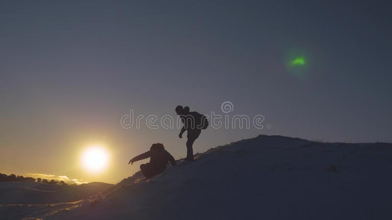 Silhouettes of men descending from high snowy mountain seeking adventure in glare of setting sun in winter. Concept of royalty free stock photo
