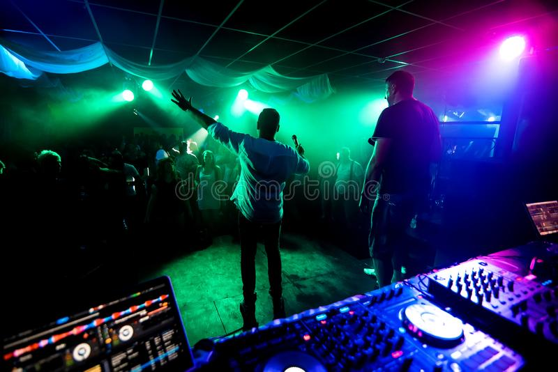Silhouettes of men leading musicians on dance floor at night club concert royalty free stock images
