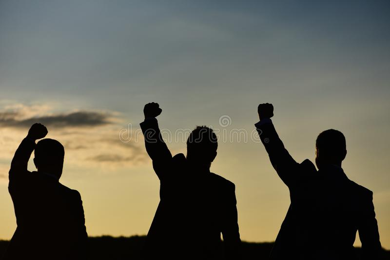 Silhouettes of men putting their fists up. Figures expressing confidence royalty free stock images